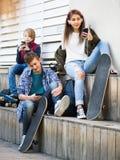 Adolescencias activas que juegan en smarthphones y que escuchan la música Foto de archivo
