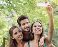 Adolescencias alegres en el parque que toma selfies Fotografía de archivo libre de regalías