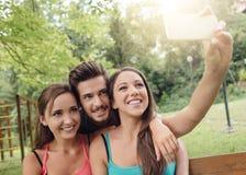 Adolescencias alegres en el parque que toma selfies Fotografía de archivo