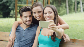 Adolescencias alegres en el parque que toma selfies Imagen de archivo libre de regalías