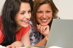 Adolescencias alegres que hojean en Internet Imágenes de archivo libres de regalías