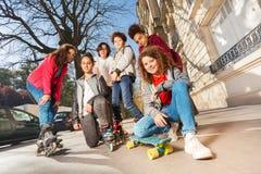 Adolescencias con el monopatín o rollerblades en paisaje urbano Imagen de archivo
