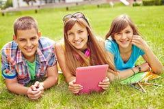 Adolescencias con el panel táctil Imagen de archivo libre de regalías
