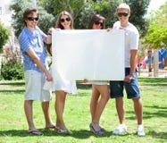 Adolescencias con la cartelera blanca que se coloca en parque Imagen de archivo libre de regalías