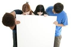 Adolescencias con la muestra en blanco Fotos de archivo
