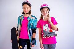 Adolescencias con los monopatines y los rollerskates Fotos de archivo libres de regalías