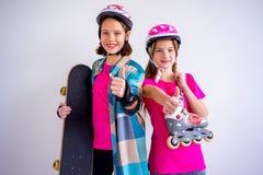 Adolescencias con los monopatines y los rollerskates Foto de archivo