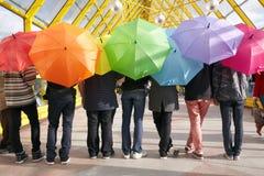 Adolescencias con los paraguas abiertos. concepto del arco iris Fotos de archivo libres de regalías