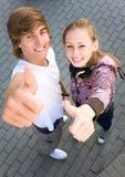 Adolescencias con los pulgares para arriba Imagen de archivo