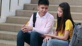 Adolescencias de la muchacha y del muchacho que juegan la sonrisa con smartphone almacen de video