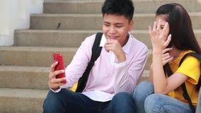 Adolescencias de la muchacha y del muchacho que juegan la sonrisa con smartphone metrajes