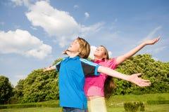 Adolescencias de la sonrisa que relajan la colocación abierta de las manos Fotografía de archivo