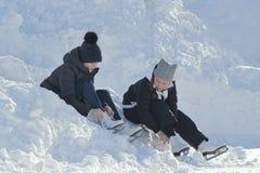 Adolescencias de las muchachas que llevan los patines que se sientan en una nieve acumulada por la ventisca cerca de la pista y q Fotografía de archivo