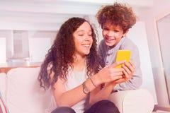 Adolescencias de risa que practican surf Internet usando el teléfono celular Fotografía de archivo