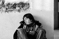 Adolescencias del muchacho que se sientan en el suelo solamente en ciudad Fotografía de archivo libre de regalías