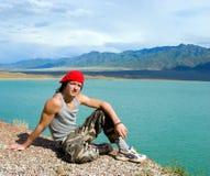 Adolescencias del muchacho que se sientan por un lago hermoso Fotografía de archivo libre de regalías