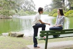 Adolescencias en banco de parque Imagen de archivo libre de regalías