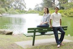 Adolescencias en banco de parque Fotografía de archivo