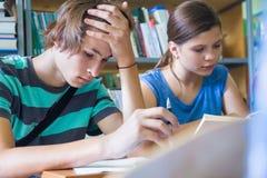 Adolescencias en biblioteca Fotos de archivo libres de regalías