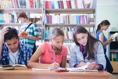 Adolescencias en biblioteca Imágenes de archivo libres de regalías