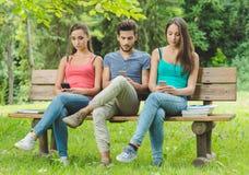 Adolescencias en el parque usando los teléfonos elegantes Foto de archivo