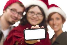Adolescencias en los sombreros de Santa que sostienen el teléfono elegante en blanco Imagenes de archivo
