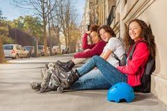 Adolescencias felices con los rollerblades que se sientan en la acera Imagenes de archivo