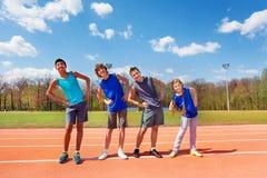 Adolescencias felices que hacen ejercicios de doblez del lado al aire libre Fotografía de archivo