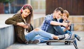 Adolescencias felices que juegan en smarthphones Foto de archivo