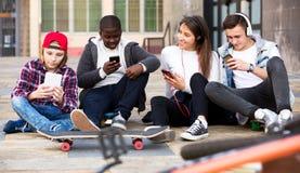 Adolescencias felices que juegan en smarthphones Fotos de archivo libres de regalías