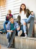 Adolescencias felices que juegan en smarthphones y que escuchan la música Fotografía de archivo