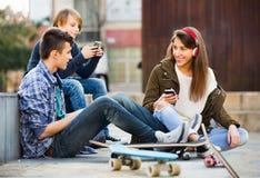 Adolescencias felices que juegan en smarthphones y que escuchan la música Imagen de archivo libre de regalías