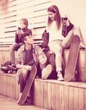 Adolescencias felices que juegan en smarthphones y que escuchan la música Imagen de archivo
