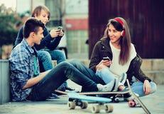 Adolescencias felices que juegan en smarthphones y que escuchan la música Imágenes de archivo libres de regalías