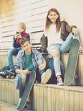 Adolescencias felices que juegan en smarthphones y que escuchan la música Foto de archivo