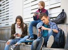 Adolescencias felices que juegan en smarthphones y que escuchan la música Fotos de archivo libres de regalías