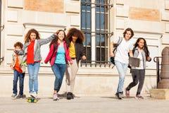 Adolescencias felices que se divierten en el campus de la universidad Fotos de archivo libres de regalías