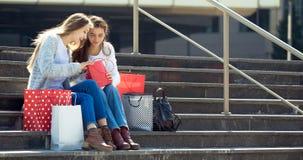 Adolescencias femeninas que se sientan en la calle con los panieres Fotos de archivo