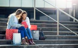 Adolescencias femeninas que se sientan en la calle con los panieres Fotos de archivo libres de regalías