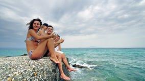 Adolescencias jovenes alegres que se sientan por el océano en el embarcadero el vacaciones de verano Foto de archivo libre de regalías