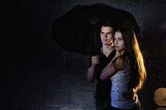 Adolescencias jovenes de los pares con el paraguas negro Imagen de archivo libre de regalías
