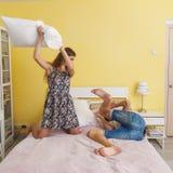 Adolescencias jovenes de los pares, lucha de almohada Fotos de archivo