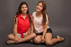 Adolescencias latinas lindas que se sientan Imagen de archivo libre de regalías