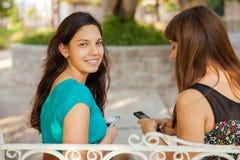 Adolescencias latinas que mandan un SMS en un parque Imagen de archivo
