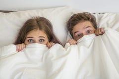 Adolescencias muchacho y muchacha en cama Fotografía de archivo libre de regalías