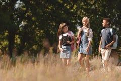 Adolescencias multiétnicas que caminan en parque Imagen de archivo libre de regalías