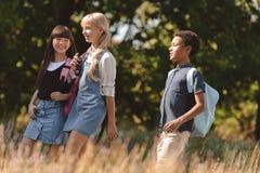 Adolescencias multiétnicas que caminan en parque Fotografía de archivo