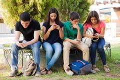 Adolescencias ocupadas con los teléfonos celulares Imagenes de archivo