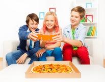 Adolescencias positivas que sostienen los vidrios con el jugo en el sofá Imagenes de archivo