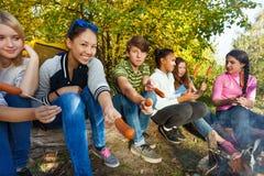 Adolescencias que asan a la parrilla las salchichas que se sientan cerca de la tienda amarilla Imágenes de archivo libres de regalías